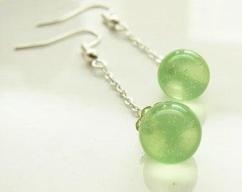 Green dangling ball earrings