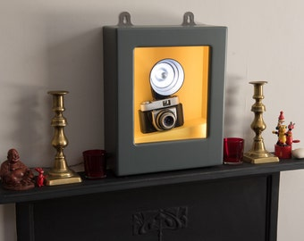 Wall light or table lamp with vintage camera and flashgun in illuminated display cabinet