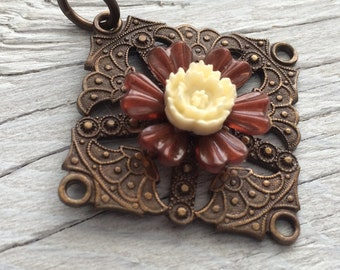 Antiqued brass pendant with cream and brown flowers 45mm