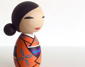 Kokeshi doll. Kimono girl in Orange