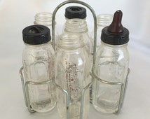 Vintage doll sized Evenflo glass advertising baby bottles in metal caddy