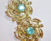 vintage gold tone swirls with pale green ish blue rhinestone center clip on earrings 14IN
