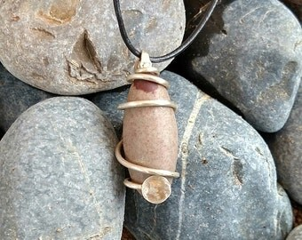 Earth Seed - This Spiral Seed Pendant features a Shiva Lingam stone Spiral wrapped in Silver wire with a hammered Silver disk accent.