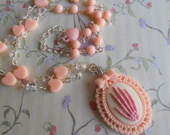 Pink skeleton hand necklace with peach heart beads