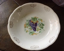 Vintage white serving bowl has a cluster of grapes with leaves inside and a gold pattern around the edge collector