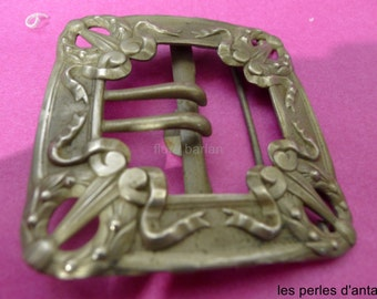 an old belt buckle in silver metal