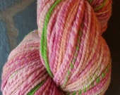 Hand spun and hand painted domestic wool yarn. Aran weight. Pinks with brite green accent. 260 yards, 2 ply.