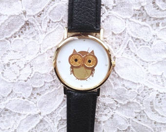 Gold owl watch with black strap.