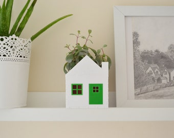 Green and white little house planter ideal for succulents
