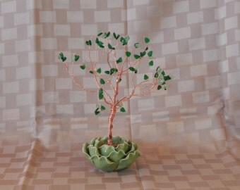 Tree sculpture with green leaf shaped glass beads sitting in a delicate lettuce leaf base