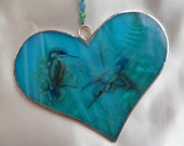 Iridescent, streaky turquoise stained glass heart decoration with purple butterfly.