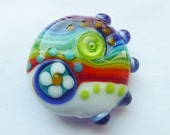 Focal glass lampwork bead with stripes.
