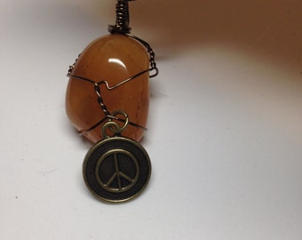 Bronze wire wrapped carnelian healing crystal pendant with peace sign charm necklace