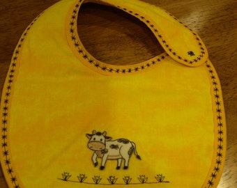 Yellow baby bib with cow