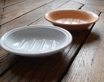 Two French vintage soap dishes, one white, one peach