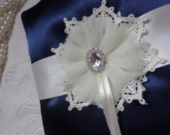 Navy blue satin ring pillow bearer is decorated with ivory satin ribbon, lace and tulle flower with clear rhinestone in the center