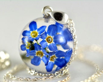 Pendant with natural forget-me-not flowers in resin sphere on a silver chain. Sphere 1.7 cm. Chain 45 cm.