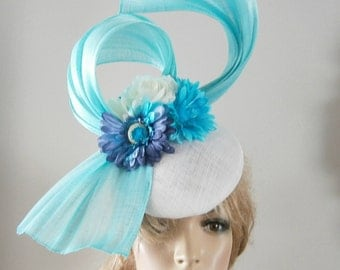 a white & pale turquoise perching beret hat with silk abaca sculpture and a spray of flowers