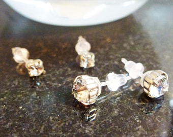 Clear faceted stud earrings with plastic posts and soft rubber backs for sensitive ears