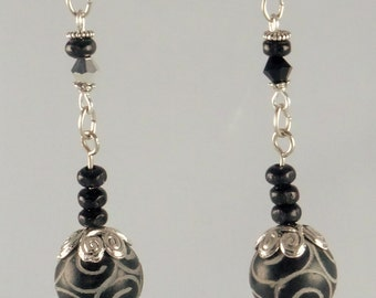 Stone and wood earrings: carved black jade (gemstone), silver details, wood beads and bicolor crystal bicone black-silver
