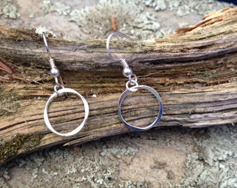 Dainty forged round silver dangle earrings.