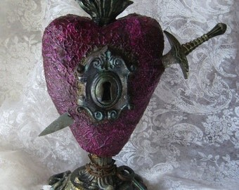 """REMAIN. A flaming heart assemblage sculpture with 7 inch sword, metal keyhole, chain, and key, vintage stand, cast clay flame, 8 1/2"""" tall"""