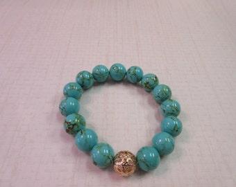 Large Turquoise beaded bracelet with gold bali bead.