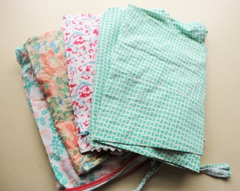 lot of four vintage feedsack aprons and a small pillow case for crafting