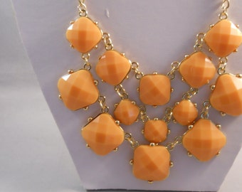 3 Row Bib Necklace with Peach Color Beads in Gold Tone Frames on a Gold Tone Chain