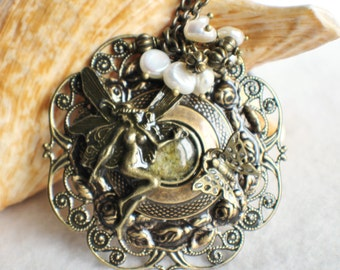 Fairy pendant with layers of bronze rings and floral filigree, with bronze butterfly and cream freshwater pearls