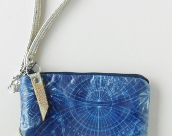 Wristlet or clutch in laminated cotton with leather trim.  Silver leather trim on laminated fabric wristlet or clutch.