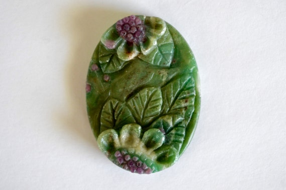 Carved stone pendant flower ruby in fuchsite hand