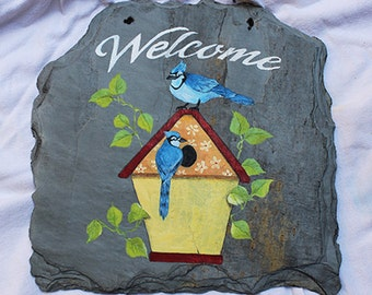 Hand painted slate birdhouse welcome sign with perched bluejays.