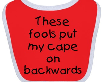 These Fools Put my Cape On Backwards® Baby Bib by Inktastic