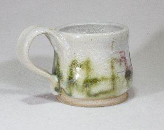 Small white stoneware mug with green and red copper underglaze decoration.