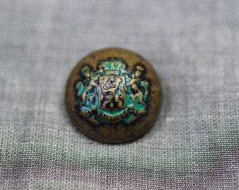 Bronze plastic button with green shield motif