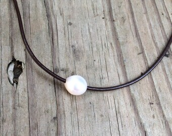 Single freshwater pearl on leather