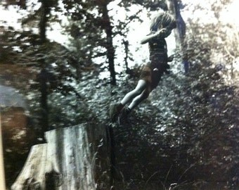 Free Flight by C. Boulter 1976. Photograph of young boy jumping off a tree stump. Just precious!