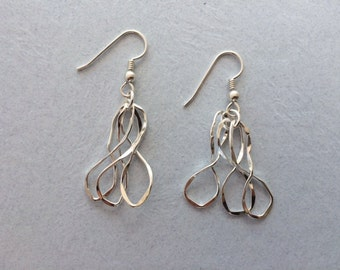 Silver dangle earrings with three infinity loops that change shape with movement.