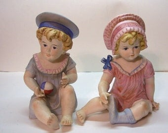 """Gebruder Heubach Bisque piano babies dressed for the beach. 9"""" high x 7"""" wide"""
