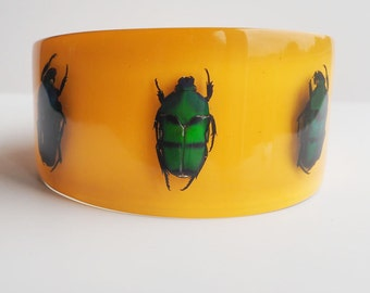 Large yellow lucite bangle with real metallic beetles