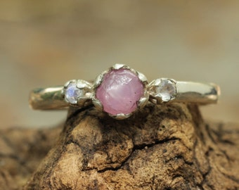 pink ruby ring with side set moonstone gems in silver band
