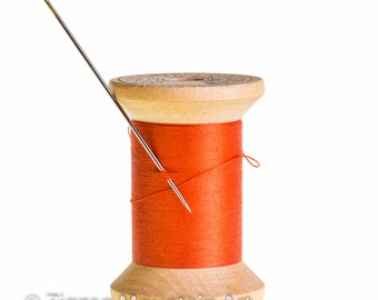 Spool of orange thread with needle.  Sewing still life wall art from still photography.  Fine art print for home decor or wall art.