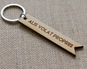 alis volat propriis with brave wings she flies latin engraved wooden keychain