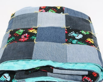 "Handmade Baby Blanket Quilt Denim and cute baby ""monsters""  assorted colors on a black background 31 1/2""  x 52 1/4"""