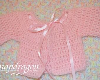 Newborn fluffy pink baby cardigan.