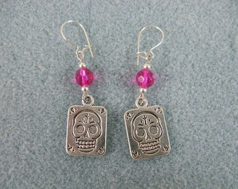 Dangle earrings with skulls and pink crystals