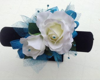 Wrist corsage and boutonniere in white roses and trimmed in Caribbean Blue