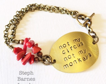 Not my circus not my monkeys bracelet in bronze with coral detail