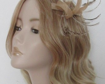 NATURAL FASCINATOR, Made of sinamay, with grizzly stripped feathers, flat,nugget beads, on a clip